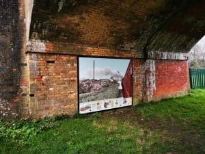 Under the arches, showing the photo board of the steam train on the track